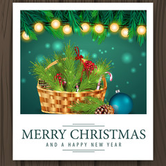 Photo with basket with Christmas tree branch and merry Christmas greetings