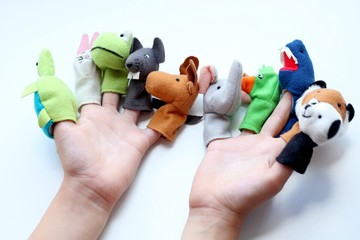 Child's hands with multi coloured toys of animals on each finger against a white background. Play with finger puppet in the nursery for children's activities concept. Happy teachers day