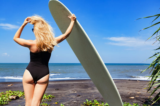Surfer girl in bikini with surfboard posing by palms on black sand beach. Young woman look at sea surf and waves. Active people in sport adventure camp, extreme activity on summer family vacation