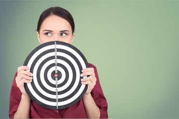 Beautiful businesswoman portrait holding round target of darts