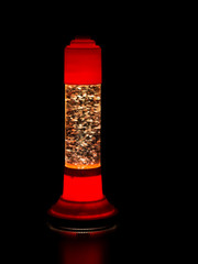 Glitter lava lamp on black background. Genuine vintage 1970 edition, red orange colour.