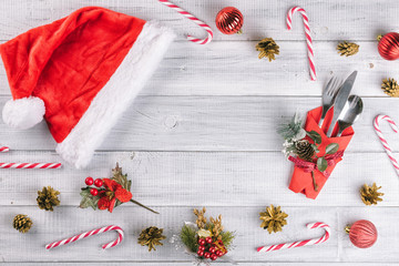 Christmas table setting with an empty plate and red Santa hat on the white wooden table. Holiday flat lay, New Year top view. Ttree decorations