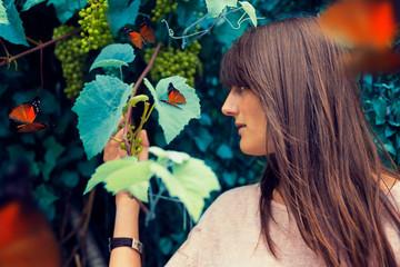 Chica en el bosque rodeada de y mariposas