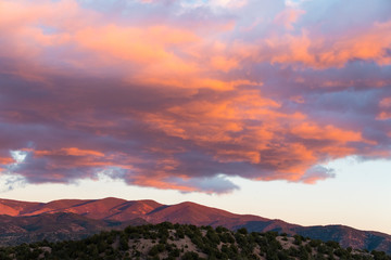 Dramatic, beautiful sunset casts purple and orange colors on clouds and the Sangre de Cristo mountains near Santa Fe, New Mexico