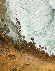 Aerial drone top view of rocky coastline on sunny summer day