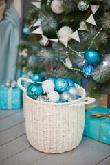 Turquoise, blue and white Christmas balls in a white basket