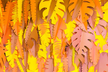 Decorative browwn paper leaves on yellow wall in the room. Details of interior