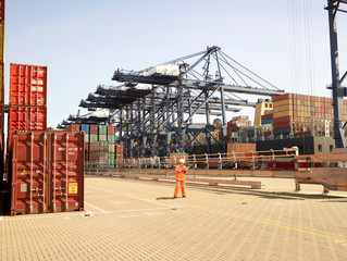Dock worker examining stack of cargo containers at Port of Felixstowe, England