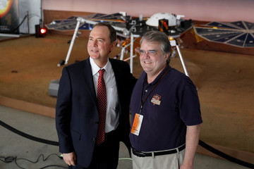 California democratic congressman Adam Schiff poses for a picture with Texas republican congressman John Culberson in front of a life size replica of the Spacecraft Insight as they visit NASA'S Jet Propulsion Laboratory