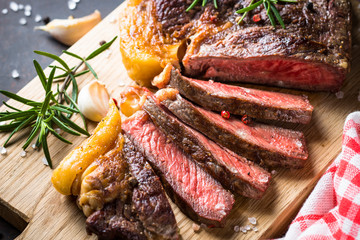 Poster de jardin Steakhouse Grilled beef steak ribeye on wooden cutting board.