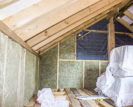 Construction - thermally insulating eco-wood frame house with wood fiber plates and heat-isolating natural hemp material. Finishing the walls with a white wooden board, using laser line level.