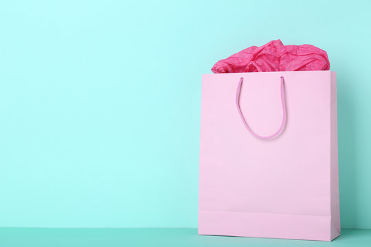 Paper shopping bag on mint background
