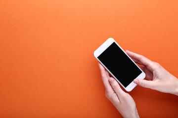 Female hands holding smartphone on orange background