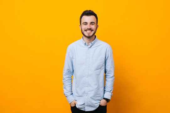 Handsome young man on yellow background looking at camera. Portrait of laughing young man with hands in pockets leaning against yellow wall. Happy guy smiling.