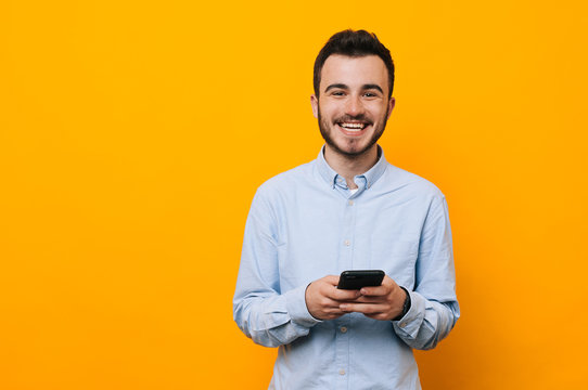 Cheerful young man in casual using phone over yellow background