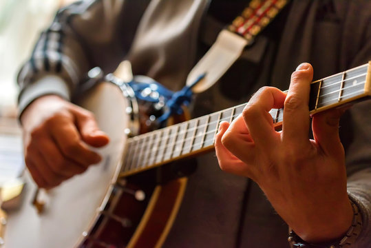 Close up hands of man playing 8-string mandolin