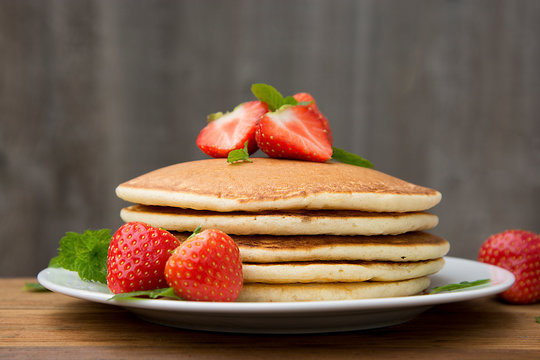 Delicious homemade american pancakes with fresh strawberry and honey. Wooden rustic background.