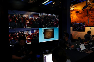 The mission control team at NASA's Jet Propulsion Laboratory (JPL) react on a video screen as the spaceship Insight, NASA's first robotic lander dedicated to studying the deep interior of Mars, sends its first picture back to JPL