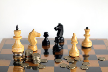 Chess pieces on board with coins.