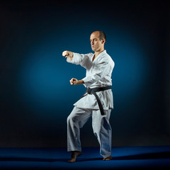 On the blue tatami athlete trains formal karate exercises