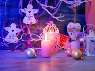 Lighted candles, decorative lights, balls, Christmas decor on a wooden table, wooden background, pink color, interior composition, romantic evening atmosphere, Christmas, new year