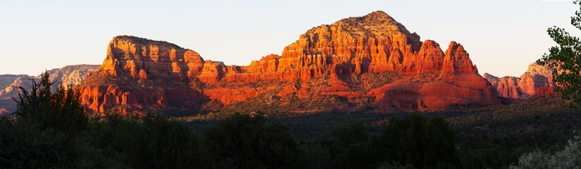 A panorama image of the red rocks of Sedona, Arizona during the golden hour at sunset.
