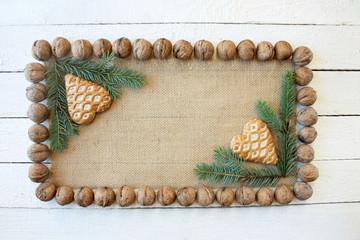 Piernikowe serca na tkaninie z juty otoczone gałęziami świerku i orzechami włoskimi, Boże Narodzenie, tło, aranżacja stołu