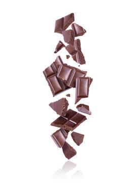Broken porous dark chocolate fall down on white background