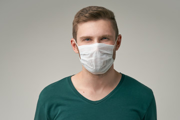 A young man with a protective medical mask with a serious expression looking at the camera. The concept of protection against infectious diseases. Wall mural