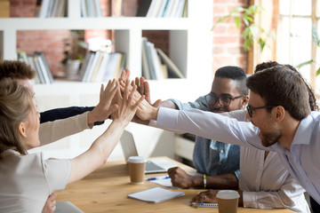 Excited happy multiracial team giving high five, celebrating good results, congratulating with success at company meeting, briefing, group of employees achieved goal, good teamwork, collaboration
