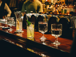 Gin tonic cocktails in glasses in bar stand