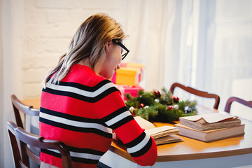 Adult caucasian girl in red sweater with books sitting at table with Christmas decoration at home.