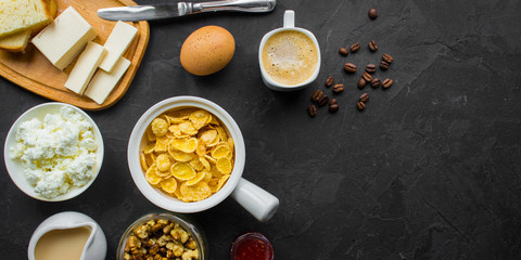 cornflakes, coffee, cottage cheese, bread, butter, eggs, jam and other ingredients for breakfast on a dark background. Top view with copy space