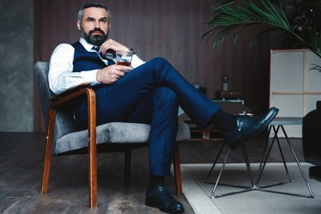 Handsome pensive man is touching his beard, looking away and thinking while sitting in armchair indoors.