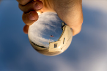 Hand holding a crystal ball with an american flag on a building with blue sky background
