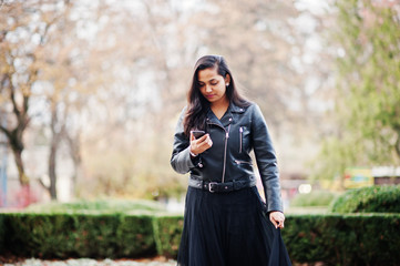Pretty indian girl in black saree dress and leather jacket posed outdoor at autumn street and looking at mobile phone.
