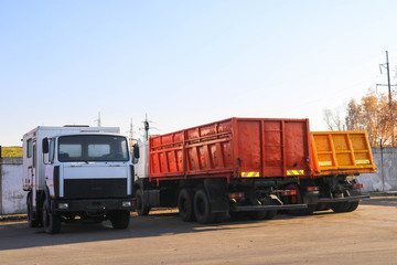Large heavy cargo trucks with cabs and trailers, dump trucks stand in a row in the parking lot ready for delivery