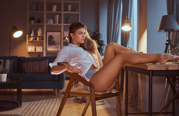 Sexy girl in a translucent blouse without underwear sits on a chair with her legs on the table at home.