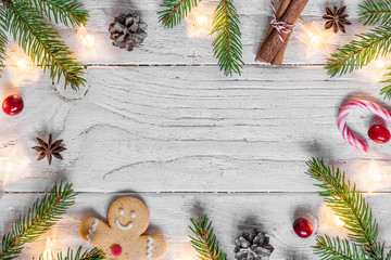 Christmas composition with christmas lights, food, fir tree, berries and pine cones on white wooden background