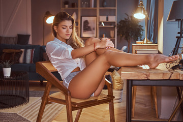 Sexy girl in a translucent blouse relaxing with closed eyes while sitting on a chair with her legs on the table at home.