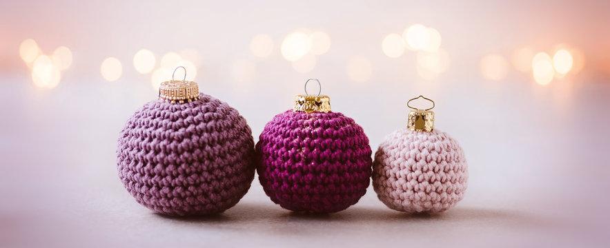 Wollige Weihnachtsgrüße - gehäkelte Weihnachtskugeln als Weihnachtsdekoration, romantisch und feminin mit Lichterbokeh im Hintergrund,  Banner-Format