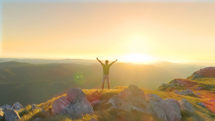 AERIAL: Cheerful man outstretches arms victoriously while observing the sunset.