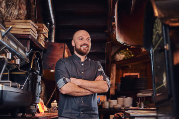 Confident chef posing with his arms crossed and looking away in a restaurant kitchen.