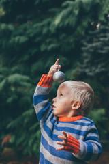 Little boy holding Christmas ball