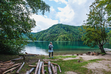 The girl on the shore of one of the most amazing lakes Plitvice in Croatia speaks on the smartphone. Pathological attachment to the means of communication