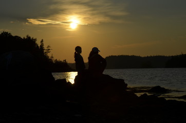 silhouette of man and woman on beach at sunset