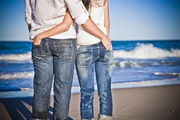 Couple in love embraced from behind on the beach