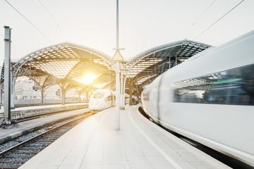 Tuinposter Spoorlijn Weiße Züge fahren in Tunnel bei Sonnenuntergang ein