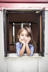 blondes Kind schaut mit nachdenklichem Blick, aus dem Fenster