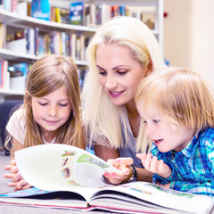 Mother with little girl and boy read book together